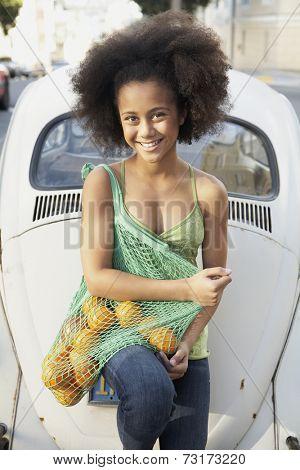 African American girl holding bag of fruit