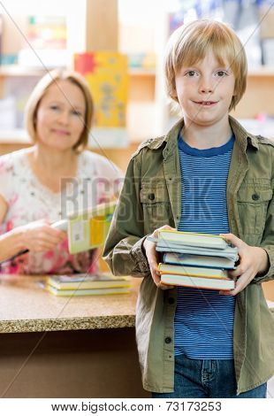 Portrait of happy schoolboy checking out books from library with librarian in background