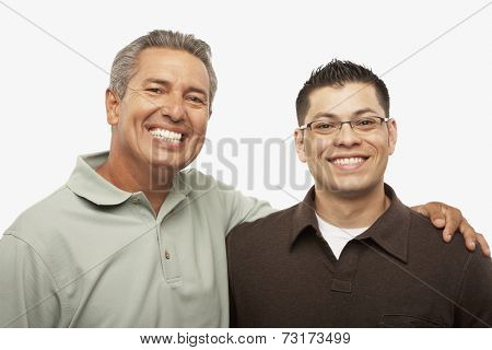 Hispanic father and adult son hugging