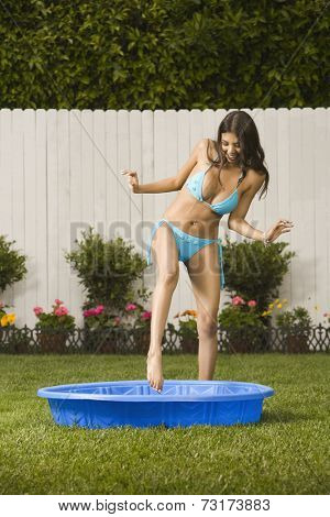 Hispanic woman stepping into kiddie pool