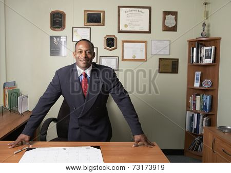 African businessman leaning on desk