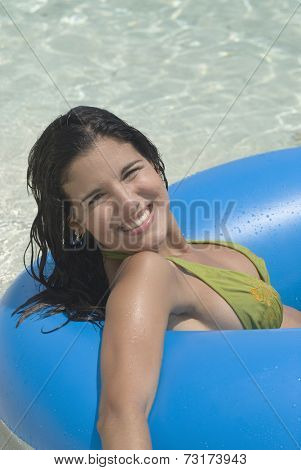 Hispanic woman on float in water