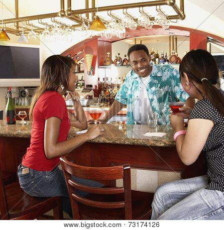 Multi-ethnic women sitting at bar