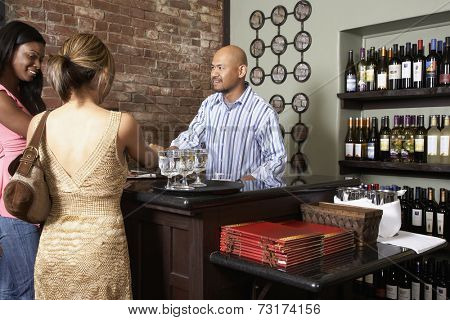 Multi-ethnic women paying at restaurant