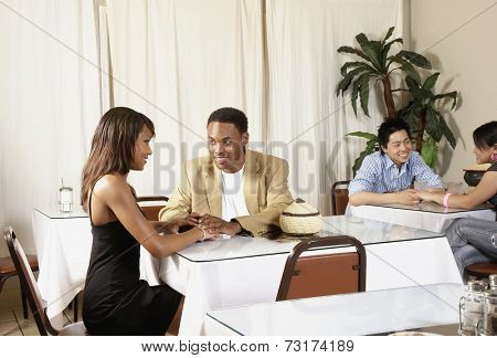 African American couple holding hands at table
