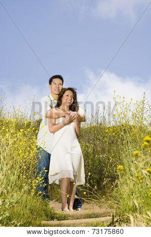 Asian couple hugging in field