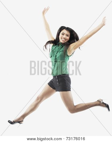 Asian woman jumping with arms raised