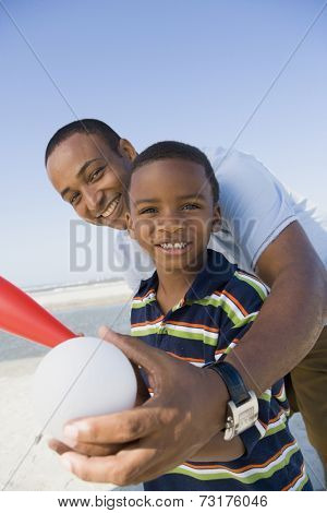 African American father and son holding baseball