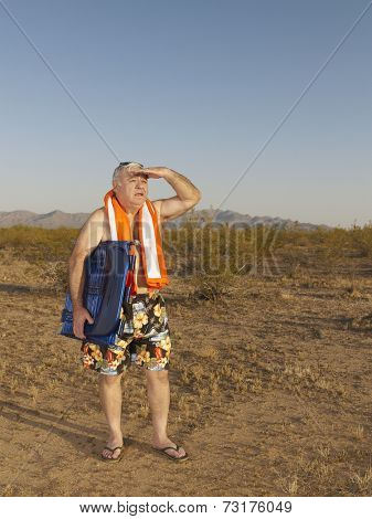 Senior Mixed Race man wearing bathing suit in desert