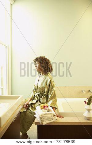 African American woman sitting on bathtub