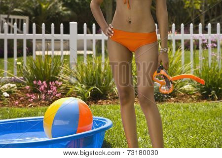 Hispanic woman in bikini next to kiddie pool