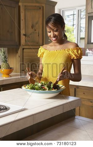 African American woman tossing salad