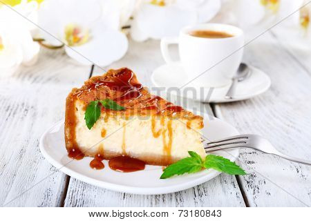 Cheese cake, orchids and cup of coffee on wooden background