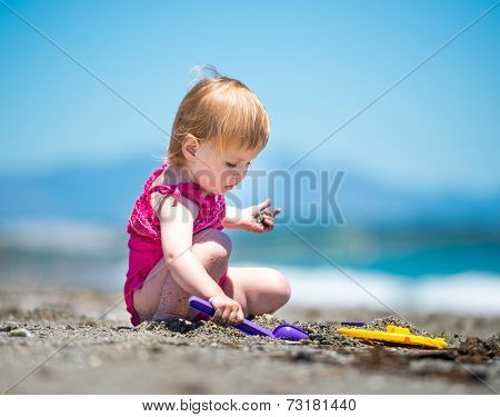 cute baby girl playing in the sand with a shovel on the beach on a beautiful summer day