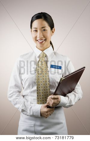 Asian woman wearing name tag and holding folder