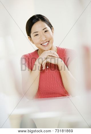 Asian woman leaning chin on hands