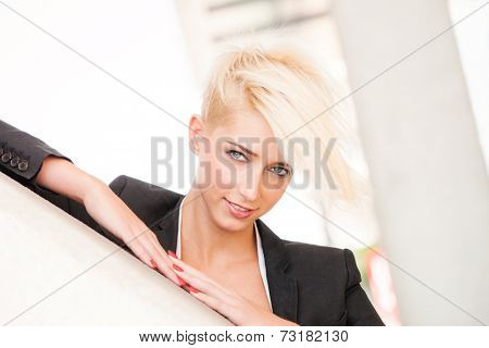smiling young blue eyes woman with short blonde hair in black blazer outdoor city portrait