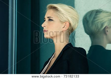 young woman with trendy short blonde hair in black blazer outdoor portrait, profile, glass reflection