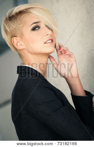 smiling young blue eyes woman with short blonde hair in black blazer outdoor portrait