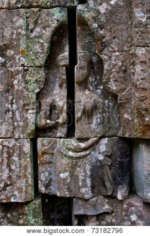 Bas-relief depicting ancient stories on the walls of  Ta Phrom temple ruins, Angkor Wat Cambodia.