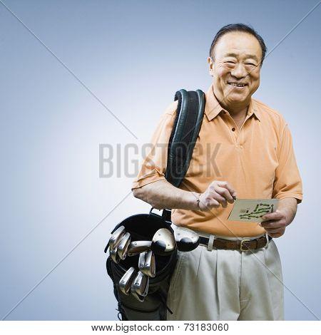 Senior Asian man carrying golf bag