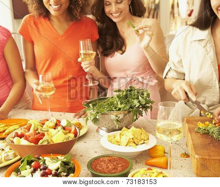 Multi-ethnic female friends preparing food