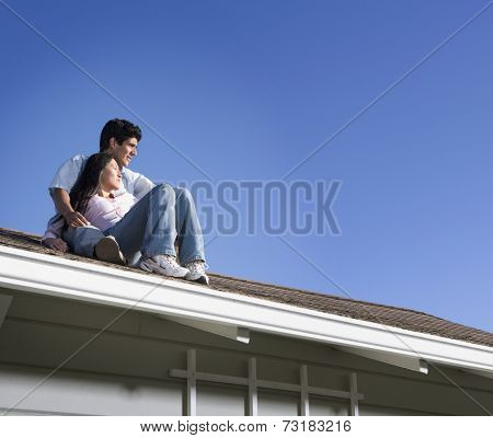 Multi-ethnic couple sitting on roof