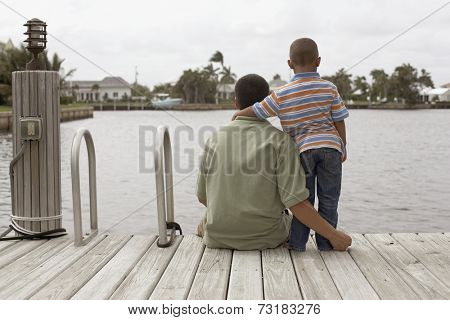 Hispanic father and son on dock