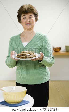 Senior Asian woman holding plate of cookies