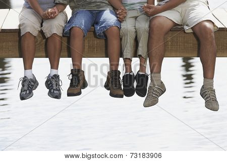 Hispanic family sitting on dock