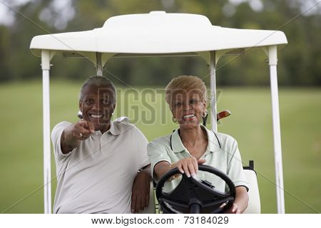 Senior African American couple driving golf cart