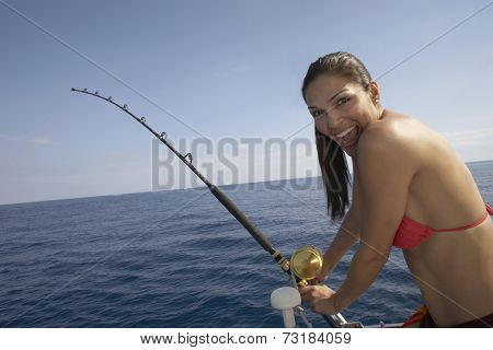 Hispanic woman fishing on boat