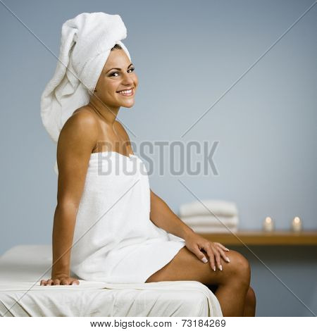 Woman sitting on spa treatment table