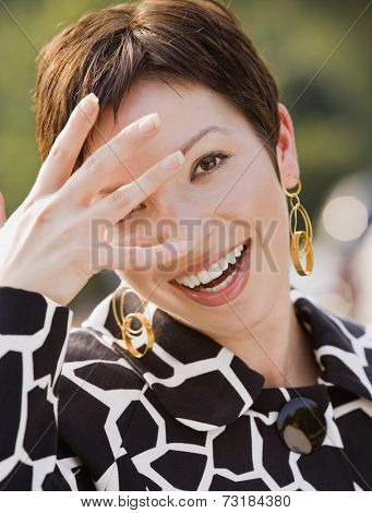 Hispanic woman with hand in front of face