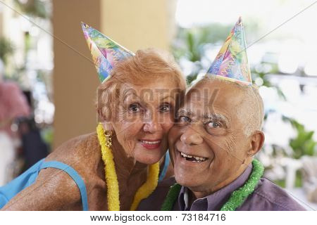 Multi-ethnic senior couple wearing party hats