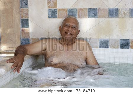 Senior Mixed Race man in hot tub