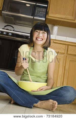 Asian woman mixing batter on floor