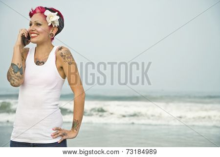 Tattooed Hispanic woman talking on cell phone