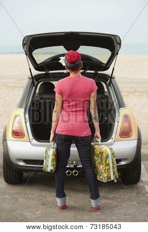 Tattooed Hispanic woman holding suitcases