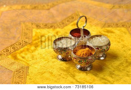 The traditional Kumkum  powder and rice grains in a tiny silver container.  Kumkum is used as a