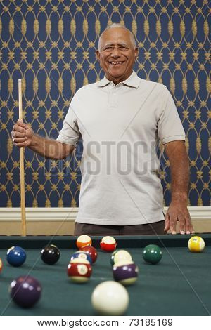 Senior Mixed Race man holding pool cue