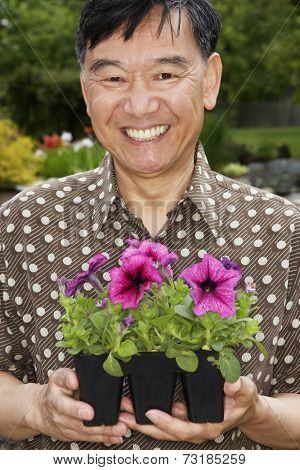 Senior Asian man holding potted plants