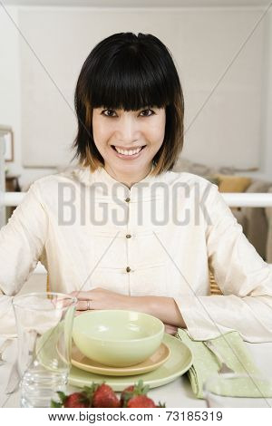 Asian woman sitting at set table