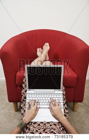 Tattooed Hispanic woman typing on laptop