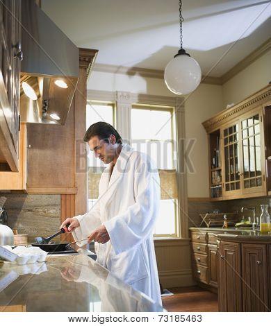 Hispanic man cooking in bathrobe