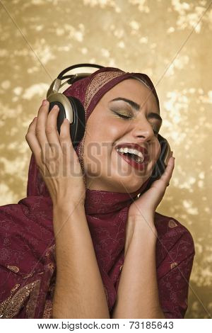 Middle Eastern woman listening to headphones