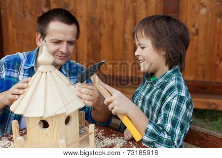 Father and son building a bird feeder together - preparing for winter