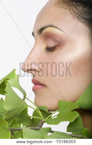 Indian woman's face next to gingko biloba plant