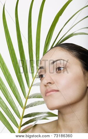 Indian woman next to palm frond