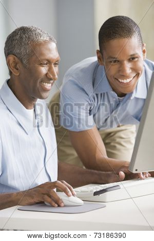 African American father and adult son looking at computer